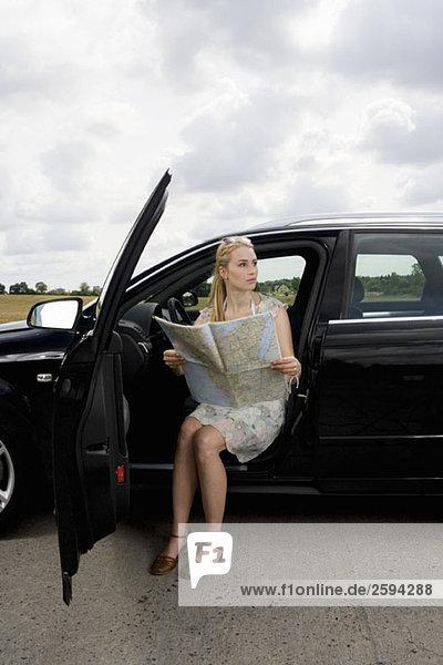 Eine Frau sitzt in einem Auto mit offener Tür und liest eine Karte.
