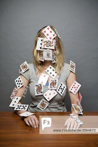 Eine junge Frau mit Karten  die überall auf ihr klebt.