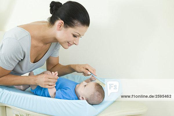 Mother combing baby's hair