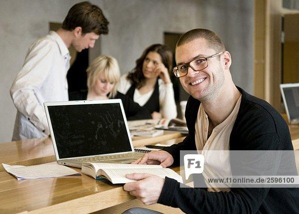 Kerl mit Buch neben dem Computer