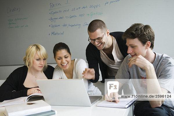 Freunde im Klassenzimmer mit Computer