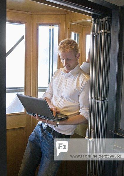 Kerl in einem Aufzug mit Computer