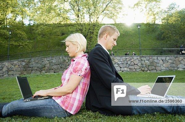 Kerl und Mädchen sitzen Rücken an Rücken in einem Park.