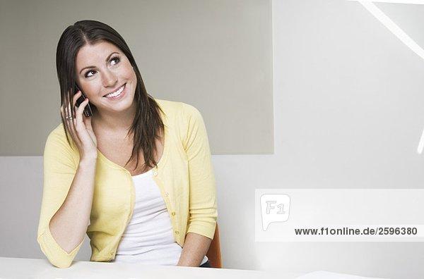Mädchen mit gelber Strickjacke spricht auf dem Handy