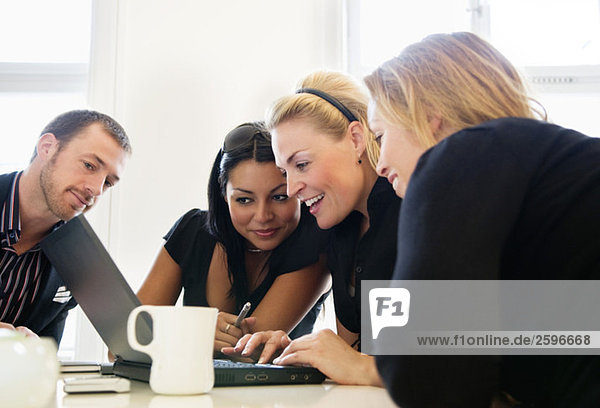 Frauen und Männer  die auf den Computer schauen
