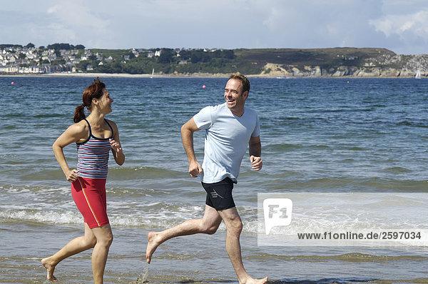 Mitte adult paar joggen am Strand