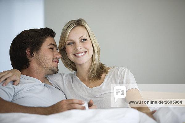 Junges Paar sitzt im Bett und trinkt Kaffee  Mann sieht Frau an  Frau lächelt