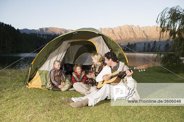 Familie mit zwei Kindern beim Camping  Vater spielt Gitarre