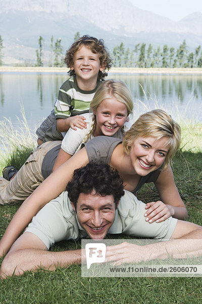 Family with two children lying on grass  human pyramid  in front of lake