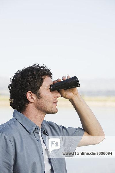 Mann sieht mit Ferngläsern in die Ferne  steht im Freien  Seitenansicht