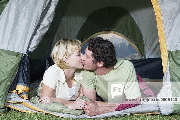Junges Paar beim Caming  liegt im Zelt und küsst sich