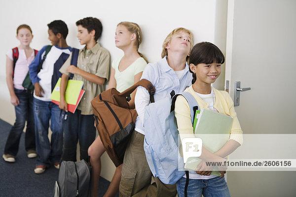 Multinationale Gruppe mit Schulkindern (10-13) warten vor Klassenraum