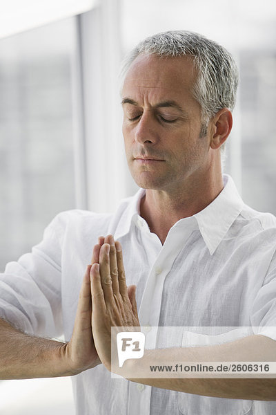 Senior man sitting, doing Yoga exercise, indoors RLX-104028