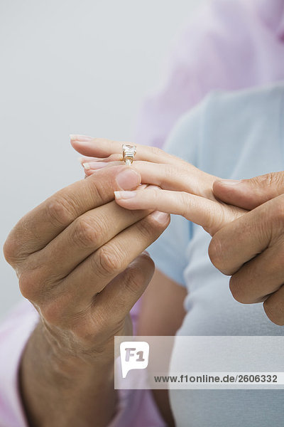 Seniorenpaar umarmt sich  Frau bekommt einen Ring an Hand  Handdetail