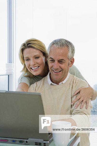Seniorenpaar lächelt und arbeitet zusammen am Laptop  Umarmung