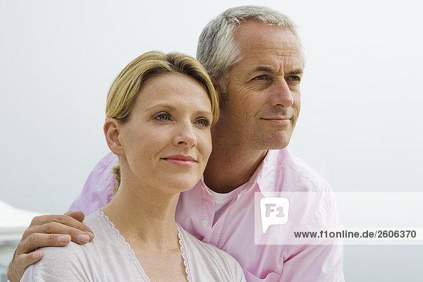 Seniorenpaar sieht verliebt in Ferne  lächelt  Umarmung