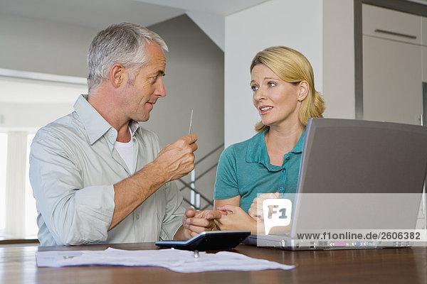 Seniorenpaar am Tisch mit Papieren Taschenrechner und Laptop  streiten