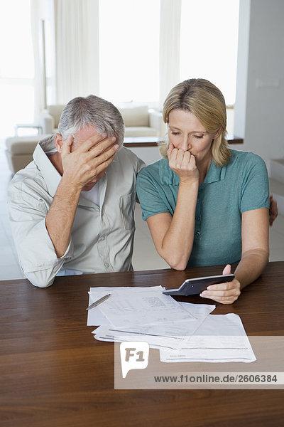 Seniorenpaar am Tisch mit Papieren Taschenrechner  verzweifelt