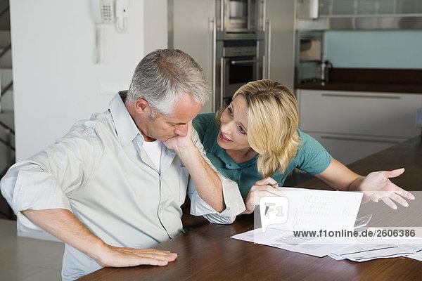 Seniorenpaar am Tisch in Küche mit Papieren Taschenrechner  streiten