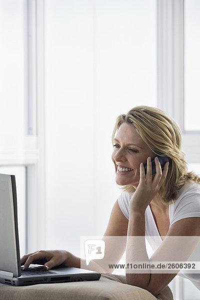 Seniorin telefoniert mit Handy und arbeitet am Laptop  lächelt