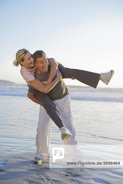 Seniorenpaar am Meer mit Wellen  Mann trägt Frau Huckepack