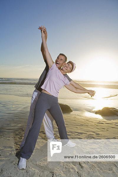 Seniorenpaar am Strand bei Sonnenuntergang stehend  umarmend