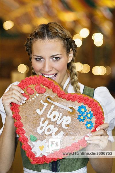 Junge Frau in Tracht steht im Bierzelt  beißt in Lebkuchenherz  Oktoberfest