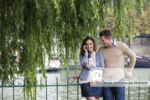 Junges Paar lehnt am Zaun an der Seine  Frau telefoniert  Paris  Frankreich