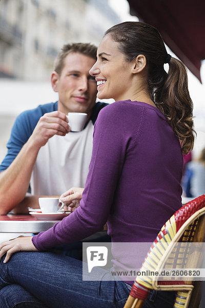 Junges Paar sitzt draußen im Cafe  Mann sieht Frau an  Paris  Frankreich