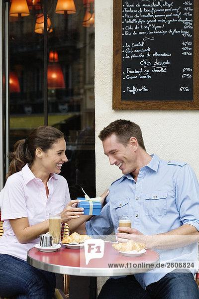 Junges Paar sitzt draußen im Cafe  Frau überreicht Geschenk  Paris  Frankreich