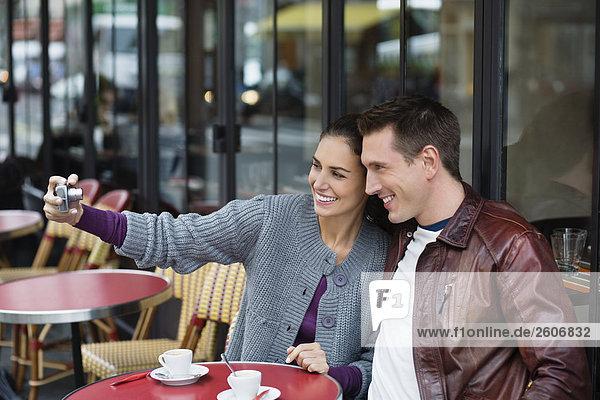 Junges Paar sitzt draußen im Straßencafe  fotografiert sich  Paris  Frankreich