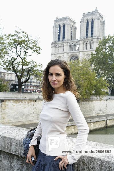 Junge Frau lehnt an Brückengeländer  vor Notre Dame  Paris  Frankreich