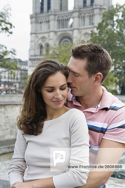 Junges Paar auf Brücke vor Notre Dame  Mann hält Frau im Arm  Paris  Frankreich