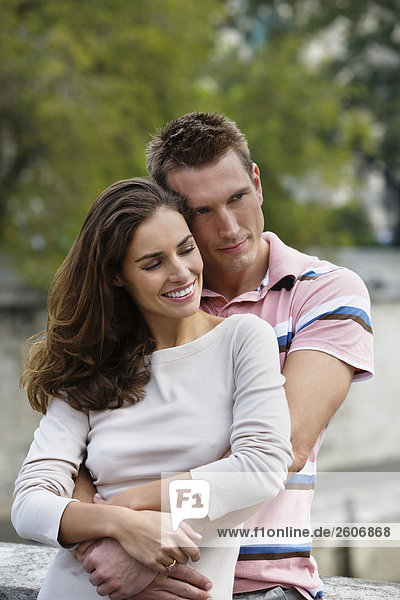 Lachendes junges Paar  Mann hält Frau im Arm  Fokus auf Paar  Paris  Frankreich