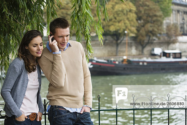 Young couple by river Seine  man using mobile phone  Paris  France
