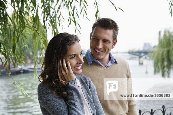 Junges Paar steht an der Seine  Frau telefoniert  Paris  Frankreich
