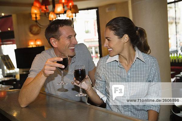 Lachendes Paar sitzt an der Theke im Cafe  trinkt Rotwein  Paris  Frankreich