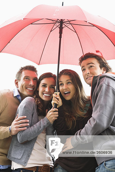 Four young people standing under an umbrella  Paris  France