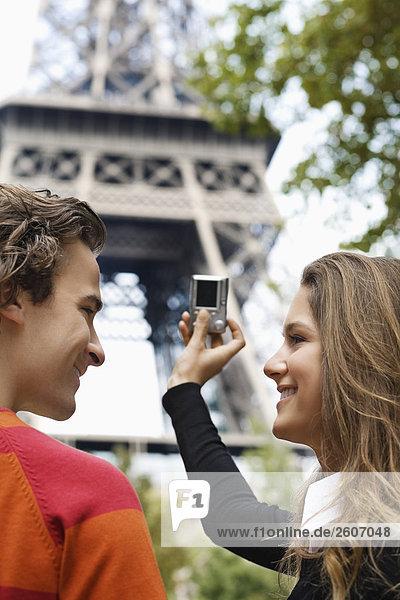 Junges Paar steht vor Eiffelturm  Frau fotografiert  Paris  Frankreich