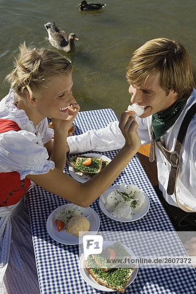 Junges Paar in Tracht sitzt am Biertisch mit Schnittlauchbrote  Radi  Obatzda und Breze  Frau füttert Mann  Biergarten am Seehaus  Englischer Garten
