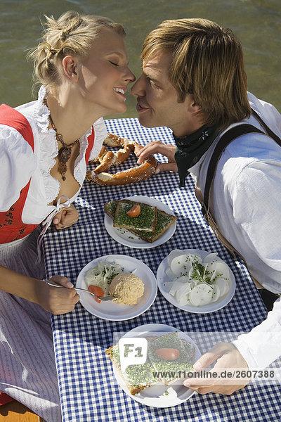 Junges Paar in Tracht küsst sich am Biertisch mit Schnittlauchbrote  Radi  Obatzda und Breze  Biergarten am Seehaus  Englischer Garten  Nahaufnahme