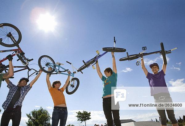 Jugendliche Jungen heben Fahrräder in die Luft