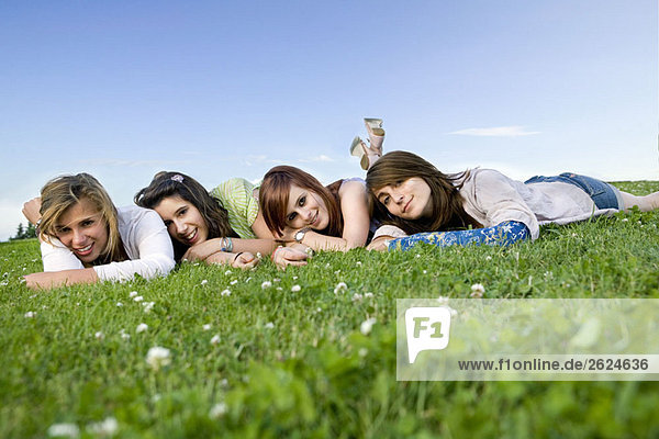 Four teen girls portrait laying on grass 07be0866