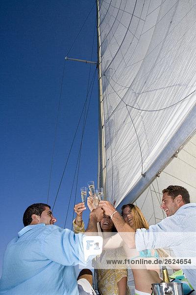 Paare machen einen Toast auf dem Segelboot