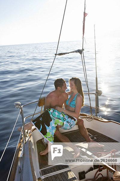 Frau auf dem Schoß des Mannes auf dem Segelboot sitzend