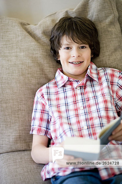 Boy laying on a couch  with a book