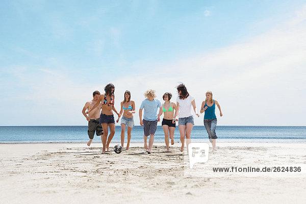 Gruppenspiel mit Ball am Strand