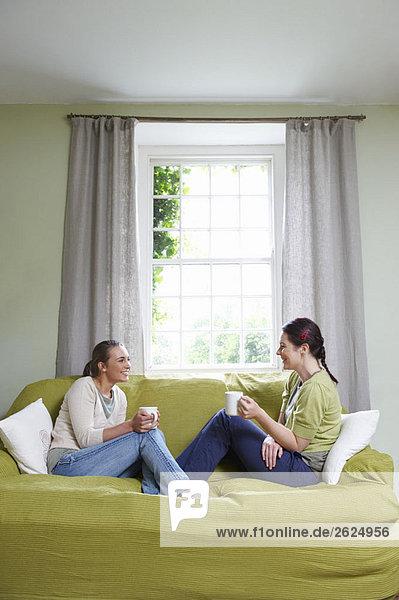 Zwei junge Frauen auf dem Sofa  mit Bechern