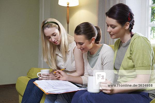 Drei junge Frauen sitzen auf der Couch.