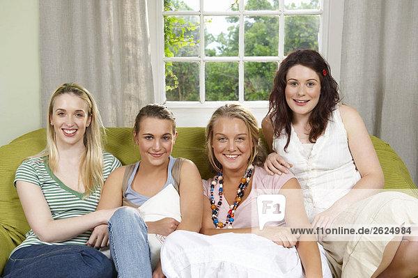 Vier junge Frauen auf der Couch sitzend